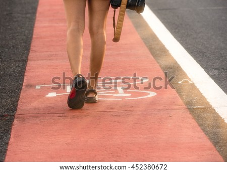 close-up women foot and leg, women  walk on bicycle way, the bicycle way is red line color, women hold camera,have fair lighting