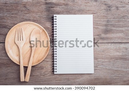 Close up wooden dish, spoon, fork and lined paper on wooden table top view - stock photo