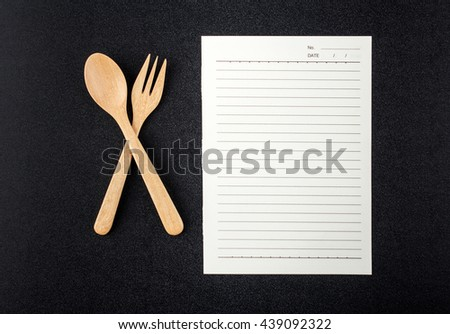 Close up wooden spoon, fork and blank paper on black table top view - stock photo