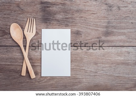 Close up wooden spoon, fork and blank paper on wooden table top view - stock photo