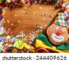 Close up Wooden Table with Colorful Carnival Streamers, Whistle, Confetti, ribbon and Doughnut with Clown Face Design. Emphasizing Copy Space at the Center. - stock photo
