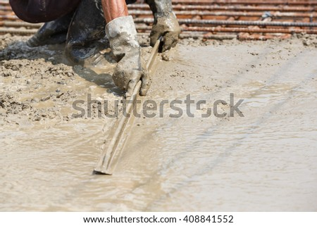 Close up worker hand using float to level surface of concrete - stock photo