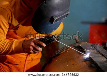 Close-up worker with protective mask welding metal. - stock photo