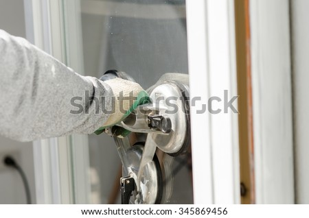 Close up worker with suction cup holding glass in sunny day. - stock photo