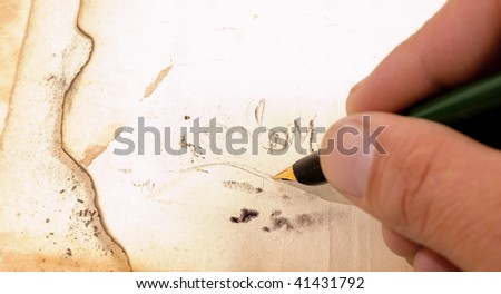 Close up writting on parchment with pen - stock photo