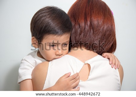 close up 3 years old Asian kid hugging his mother on white background - stock photo