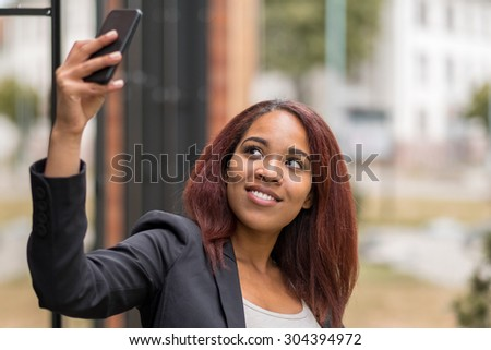 Close up Young African-American Businesswoman Taking Selfie Photo Using her Mobile Phone Outside the Office. - stock photo