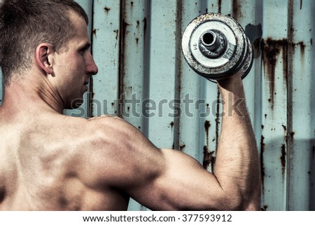 Close up young athletic man doing workout with heavy dumbbell against the background of agray metal wall - stock photo