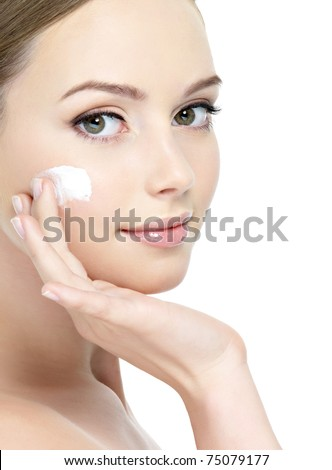 Close-up young beautiful face of girl applying moisturize cream - isolated - stock photo