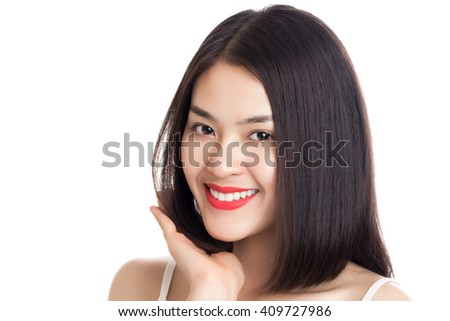 Close up young beautiful smiling Asian woman with hand touching her hair isolated on white background. - stock photo