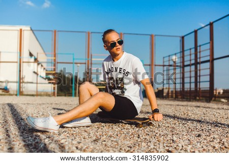 Close-up young boy relaxed and sitting on the grass and listen music on earphones,in sun reflecting bright sunglasses,denim tshirt.smiles and laughs,mans fashion style.teen fashion  - stock photo