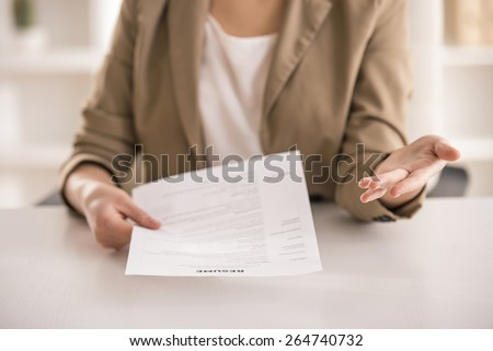 Close-up. Young businesswoman holding resume in office. - stock photo