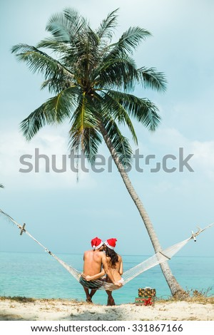 Close-up young couple sitting on a hammock under the palm trees celebrate new year on tropical hot countries with gifts and hugs,enjoy their holidays on hot countries,sea background,samui,thailand - stock photo