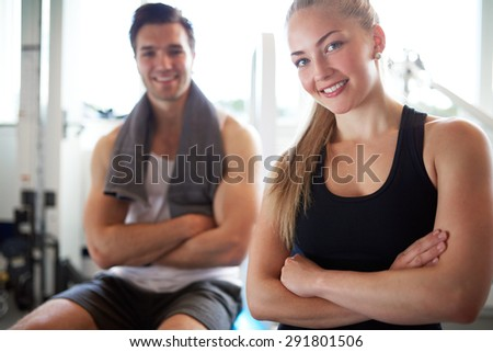 Close up Young Fit Couple Smiling at Camera After Workout inside the Gym, with Arms Crossed in front their Bodies. - stock photo
