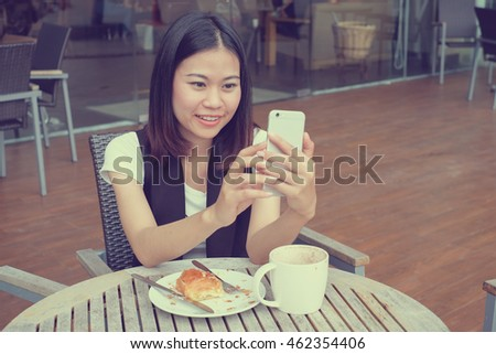 close up young girl take a selfie before have lunch at outdoor cafe restaurant:selective focus on happy woman using smartphone for checking location and upload photo on social media network concept.