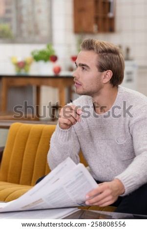 Close up Young Handsome Man in Long Sleeve Knit Outfit Sitting at Living Room with Newspaper. Capturing Him While Looking at Right Side, Emphasizing Imagination. - stock photo