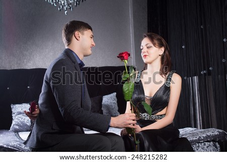 Close up Young Man Giving a Red Rose Flower to his Happy Girlfriend. Captured at the Bedroom While Both are Sitting on the Bed. - stock photo