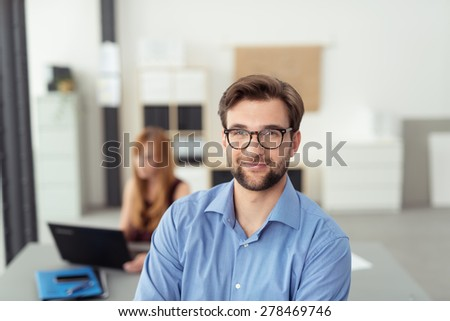 Close up Young Office Man in Glasses Standing Inside the Office and Smiling at the Camera with Busy Female Co-Worker Behind him. - stock photo