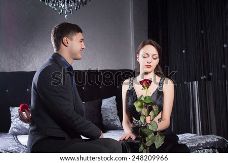 Close up Young Sweethearts, in Classy Clothes, Sitting at the Bedroom While Girlfriend is Holding a Red Rose Flower. - stock photo