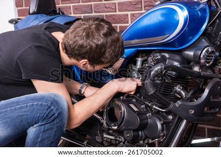 Close up Young White Guy Fixing Some Parts of his Blue Motorbike Using his Bare Hands. - stock photo