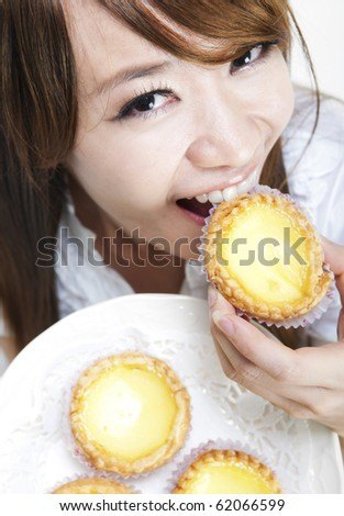Close up young woman enjoying egg tart - stock photo
