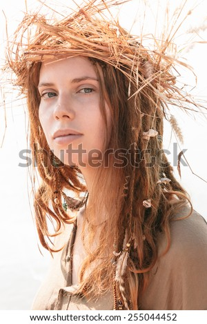 Close up Young Woman in Boho Style with Dreads Wearing Crown of Hay While Looking at the Camera. - stock photo