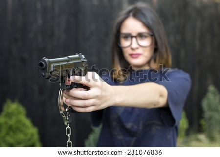 Close up Young Woman in T-Shirt Holding a Hand Gun with her Both Hands - stock photo