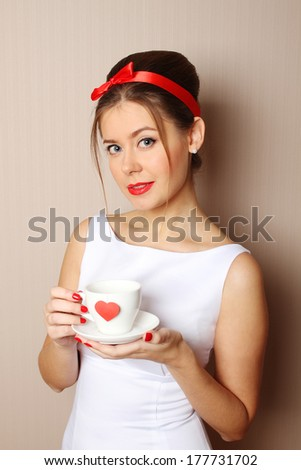 Close up young woman with a cup, which shows a red heart