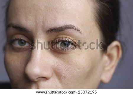 close up young woman with focus on left green eyes - stock photo