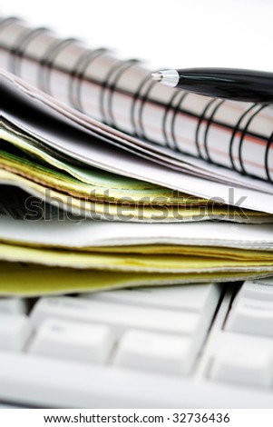 close-ups of keyboard and stack of magazines