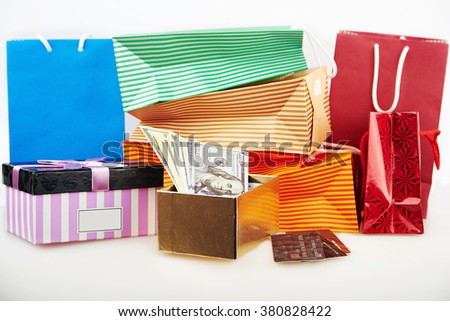 Close view ar colorful paper shopping bags and boxes with money and debit cards against white background - stock photo
