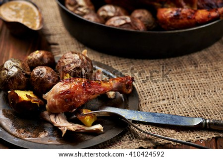 Close view at barbecued chicken leg with baked potatoes on a rustic metal plate with whole chicken and sauce on a background. Sackcloth and wooden background. Warm colors - stock photo