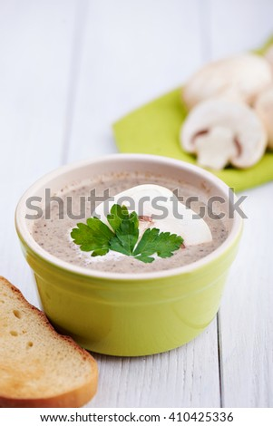 Close view at delicate cheese cream soup with mushrooms, crispy bread and spoon on a white wooden background
