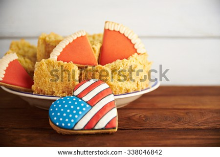 Close view at figures of gingerbread american flag in a heart shape with Thanksgiving pumpkin pie on a wooden backgroun - stock photo