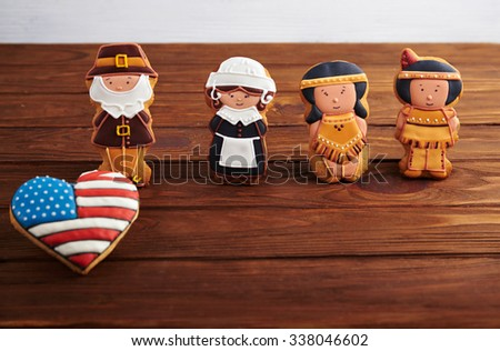 Close view at figures of gingerbread pilgrims and indians with american flag in a heart shape on a wooden background - stock photo