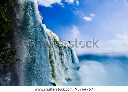 Close view from one of the water falls in Foz do Iguassu park, with a blue sky and a lot of water in the air (kind of water mist).