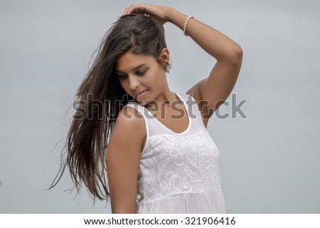 Close view of a beautiful woman on a white dress over a blue sky.