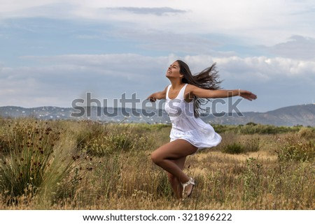 Close view of a beautiful woman on a white dress running on the meadow.