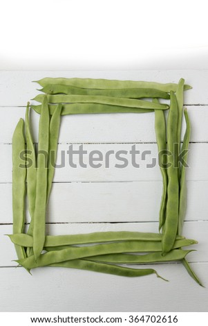 Close view of a bunch of common beans on a white wooden background. - stock photo