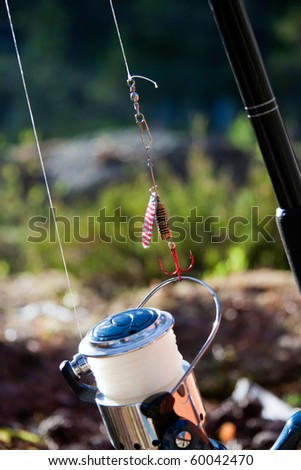 close view of a fishing rod with hook in the sunset and wilderness