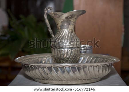 Close view of a silver baptism holy water container .