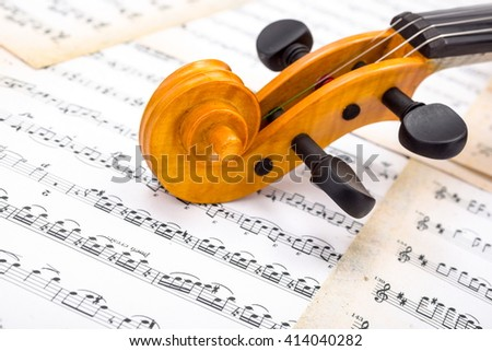 Close view of a violin scroll on musical sheet - stock photo
