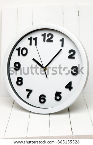 Close view of a white kitchen clock with black numbers on a white wooden background. - stock photo