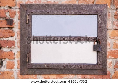 Close view of an old horizontal small door with rusty lock in a red brick wall - stock photo