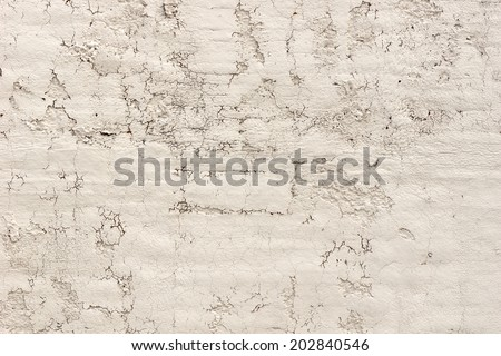 Close view of an old weathered stucco wall with cracks and damage.