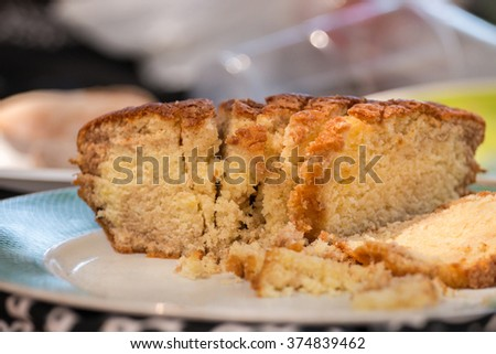 Close view of an orange cake sliced in pieces.