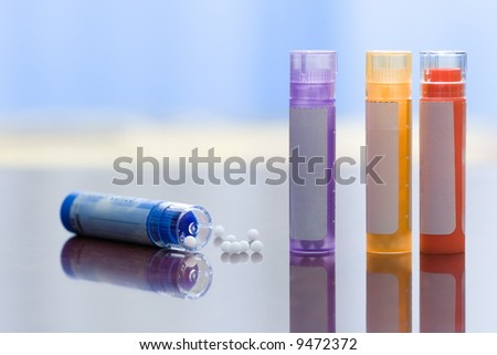 Close view of homeopathic medications - containers and small white balls