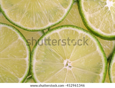 Close view of several slices of lime illuminated with natural light. - stock photo
