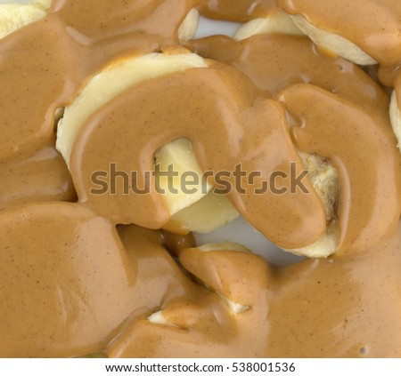 Close view of sliced bananas covered with creamy peanut butter on a plate.