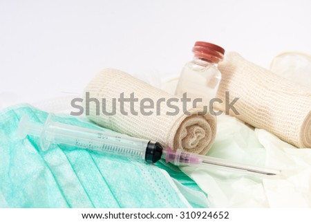 Close view of syringes and bandages on surgical mask and gloves. - stock photo